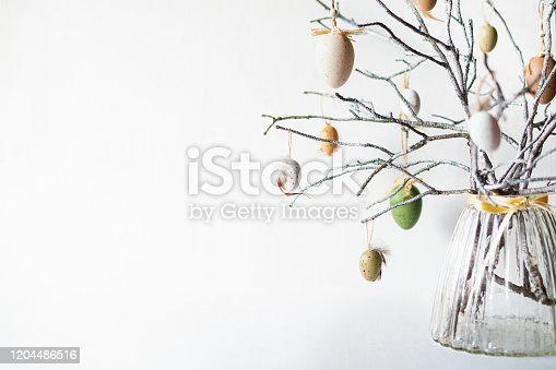 istock Still life with tree branches decorated with Easter eggs and feathers in glass vase 1204486516