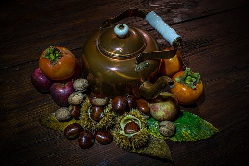 Umbria, Italia:\nNatura Morta con noci, castagne, mele, cachi e teiera su un vecchio tavolo di legno