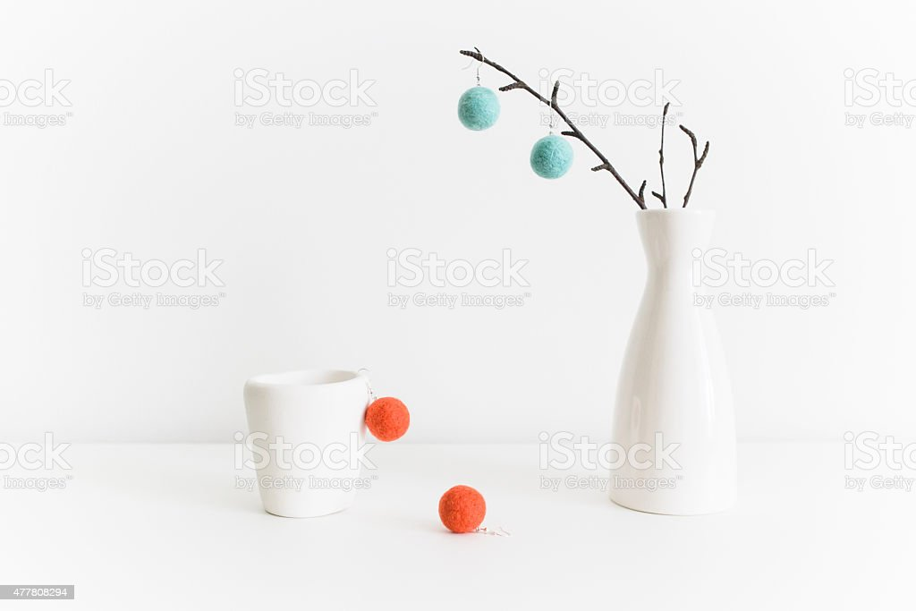 Still life with white pottery and colorful felt balls earrings stock photo