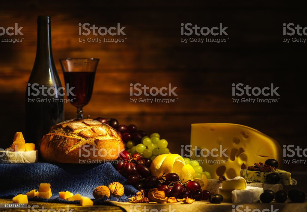 Still life with wine, grapes, bread and various sorts of cheese. стоковое фото