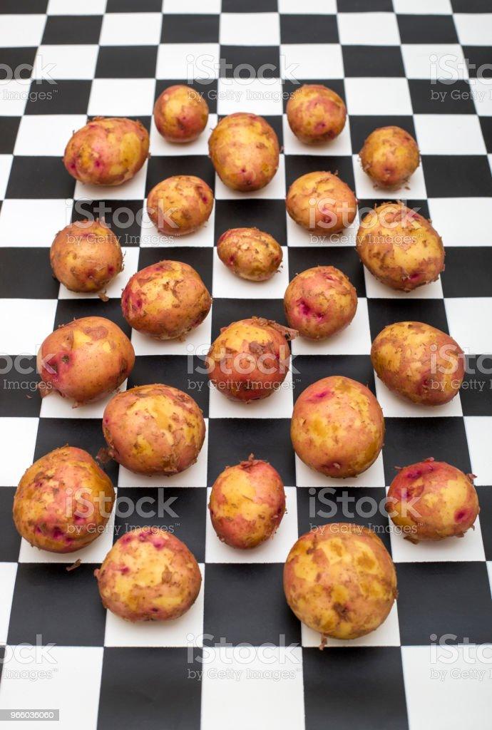 Stilleben med unga potatis på bakgrunden av svarta och vita rutor - Royaltyfri Fotografi - Bild Bildbanksbilder