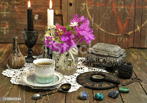 Still life with zodiac chart, black candle, cup and stones. Esoteric, wicca and occult background with magic objects, fortune telling and divination ritual, Halloween mystic background.