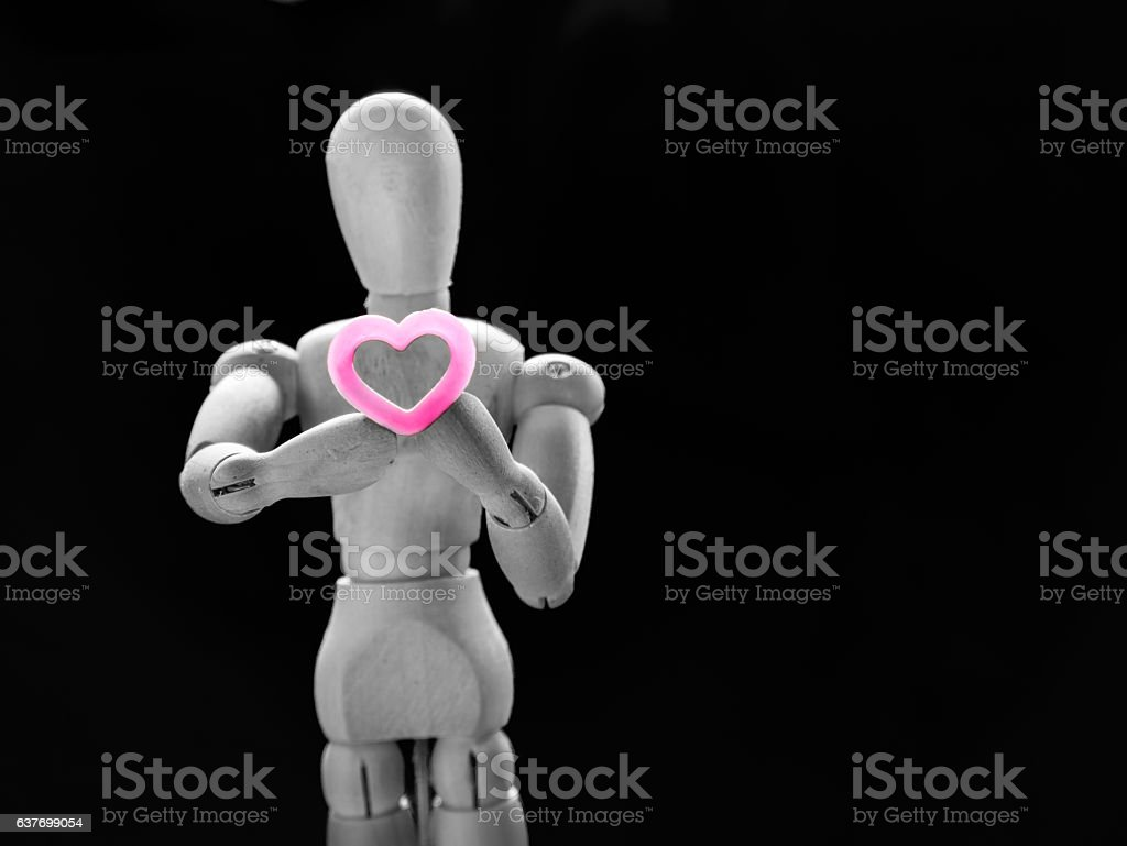 Still life wooden puppet and pink heart. stock photo