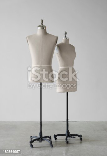 Two Mannequins photographed in a still life setting against a grey wall.