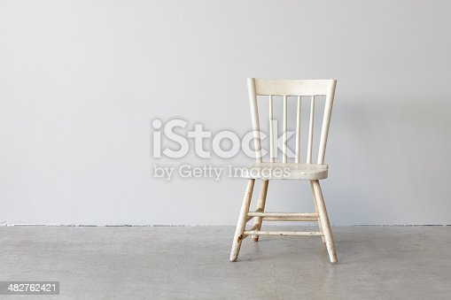 Distressed white wood chair photographed on a concrete floor against a grey wall.