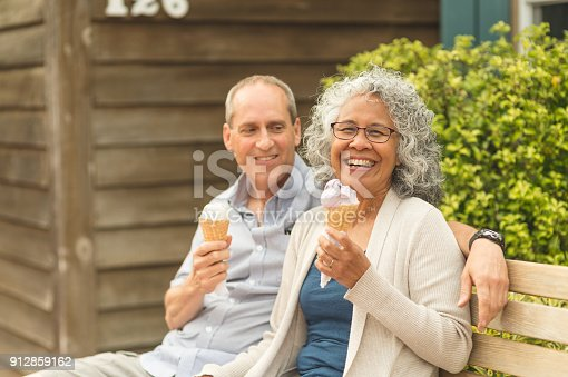 A senior couple enjoy a walk together and ice cream cones on a lovely summer afternoon. They are sitting on a park bench. He is looking at her affectionately. She is looking at the camera.