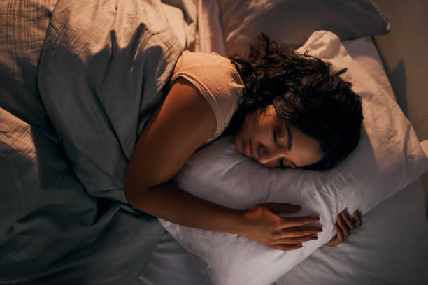 Still stuck in dream land High angle shot of a beautiful young woman sleeping in her bed at home during the night sleeping stock pictures, royalty-free photos & images