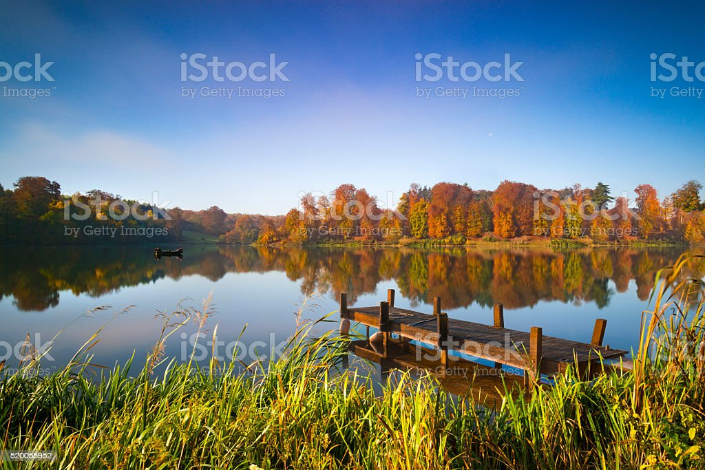 Still waters of a lake in autumn stock photo
