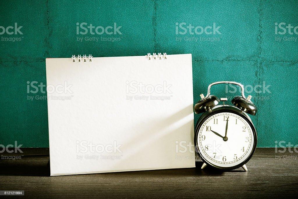 Stillife of desk calendar with alarm clock on wood table. stock photo