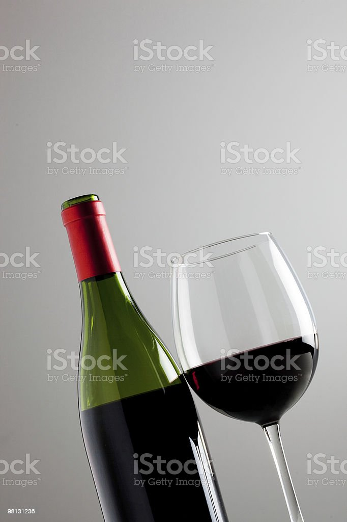 Still-life with one wine bottle and glass over grey background royalty-free stock photo