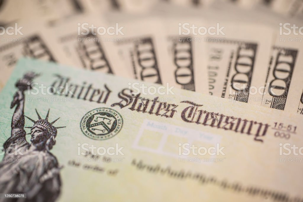 Stimulus Check The 2020 Stimulus check. Surrounded with 100 dollar bills.  Sent to US citizens during the covid-19/coronavirus pandemic Adversity Stock Photo