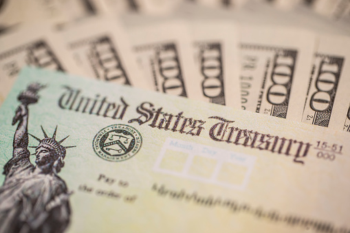 The 2020 Stimulus check. Surrounded with 100 dollar bills.  Sent to US citizens during the covid-19/coronavirus pandemic