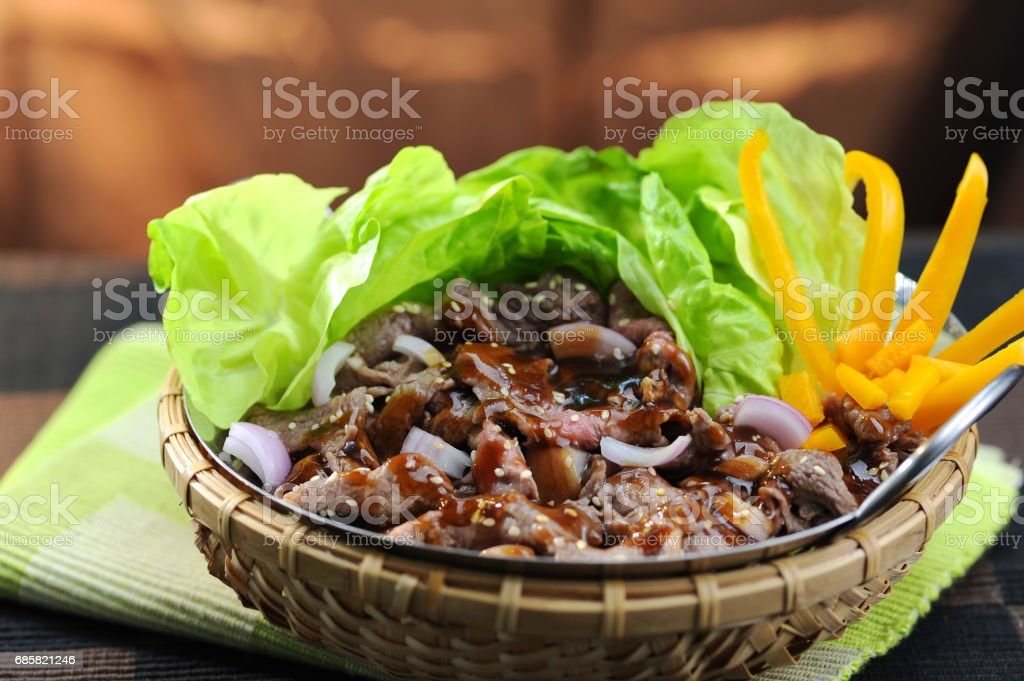 Stir fried beef with oysters, sauce and lettuce in bamboo basket stock photo