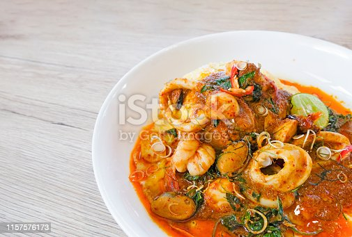 Stir fried chilli shrimp squid sea shells wrapped in thick eggs in a white dish on a wooden background from top view.