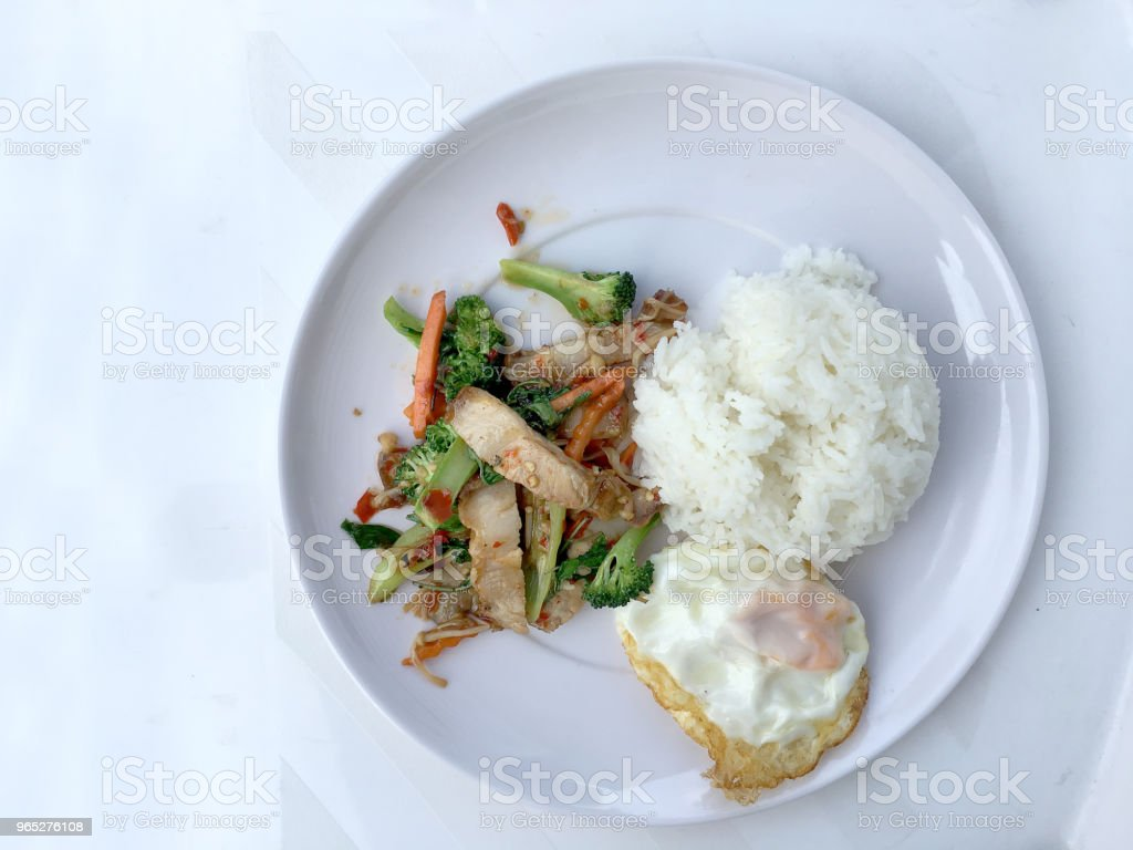 Stir Fried Crispy pork with Roasted Chili Paste and mixed vegetables;  basil; kale; broccoli; carrot; red chilli & Fried egg with Thai jasmine rice in white dish on white background. Thai style food. zbiór zdjęć royalty-free