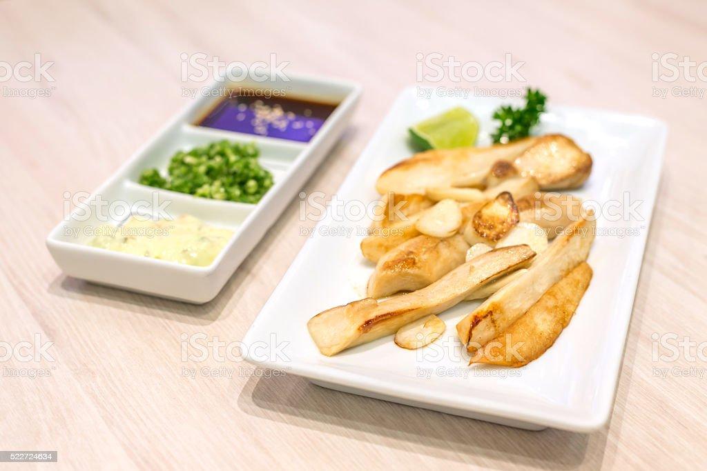 Stir fried eringii mushroom and garlic on white plate stock photo