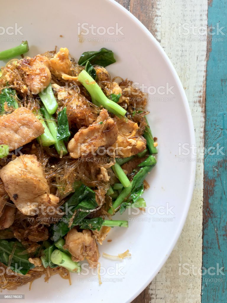 "Stir fried Flat Rice Noodle with Soy Sauce and Pork in white dish on colourful wooden table in thai called ""Pad See Eww"". Thai style food. zbiór zdjęć royalty-free"