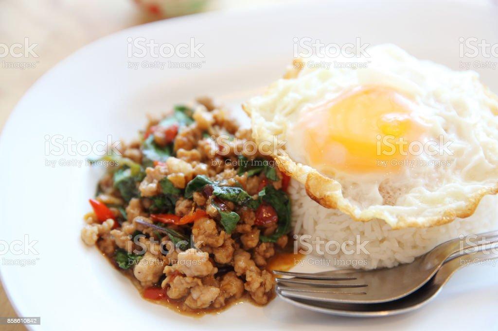 mezclar la carne de cerdo frita y albahaca con arroz y huevo en comida tailandesa fondo madera - foto de stock