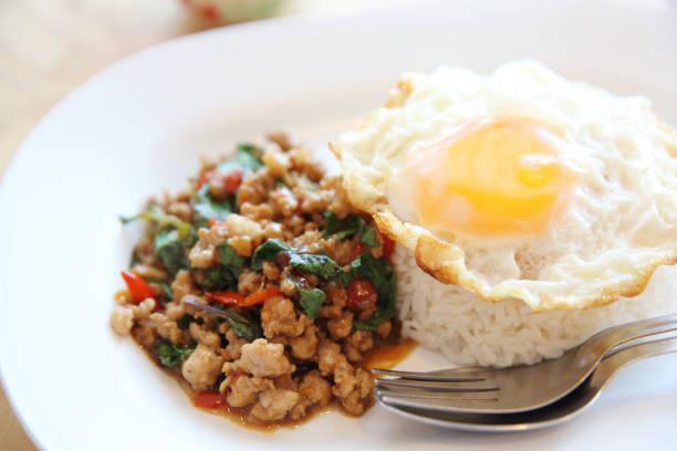 Rühren Sie gebratenes Schweinefleisch und Basilikum mit Reis und Ei auf Holz Hintergrund thai-Küche – Foto