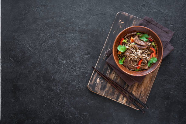 Stir fried soba noodles, beef Stir fry with soba noodles, beef and vegetables. Asian healthy food, stir fried meal in bowl on black background, top view, copy space. asian food stock pictures, royalty-free photos & images
