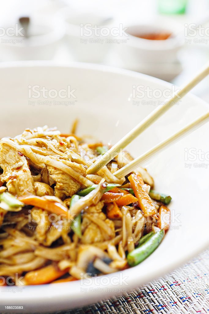 Stir fried Thai chicken with noodles, condiments in background royalty-free stock photo