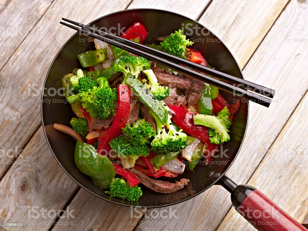 Stir fried vegetables in a mini wok with chopsticks, on wood stock photo