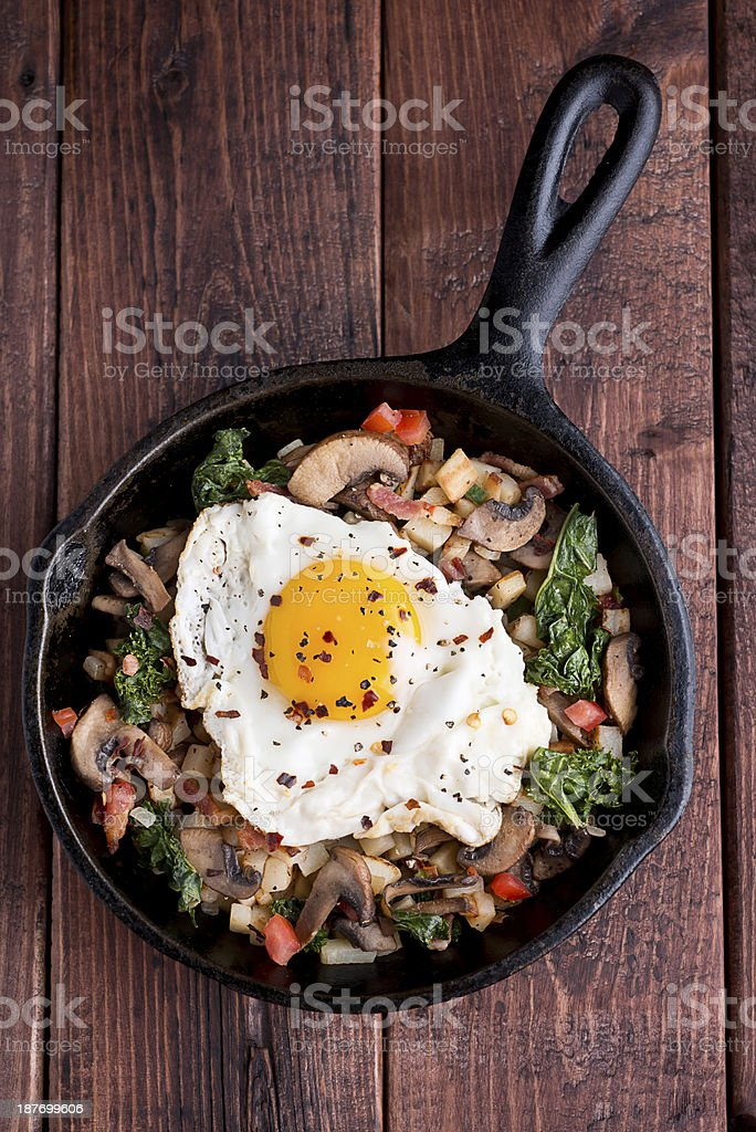 Stir fried vegetables with fried egg on top in cast iron stock photo