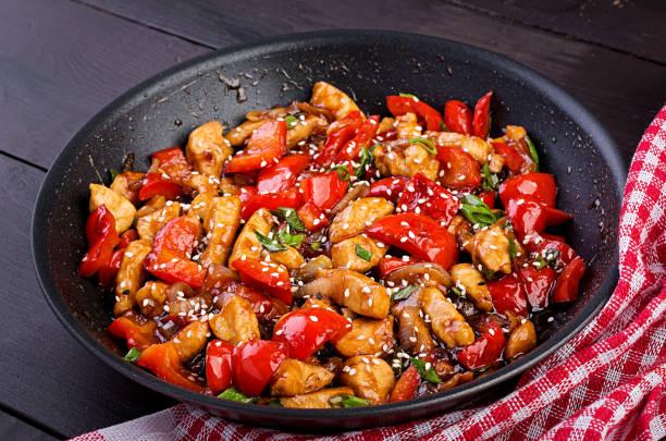Hühnchen, Paprika und grüne Zwiebeln rühren. Asiatische Küche – Foto
