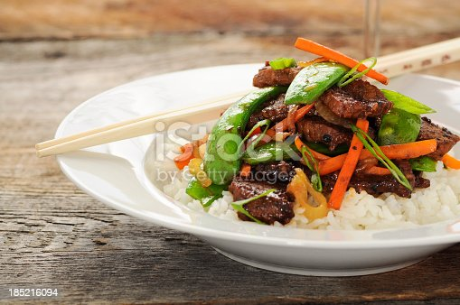 Delicious beef stir fry with carrots, snap peas and rice.