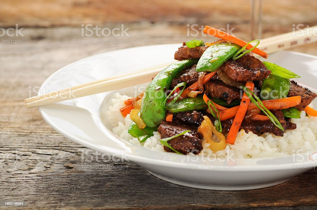 Stir fry meal including beef, peas, carrots, and rice stock photo