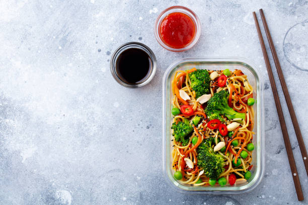 Stir fry noodles, udon with vegetables in glass lunch box. Grey stone background. Top view. Copy space. stock photo