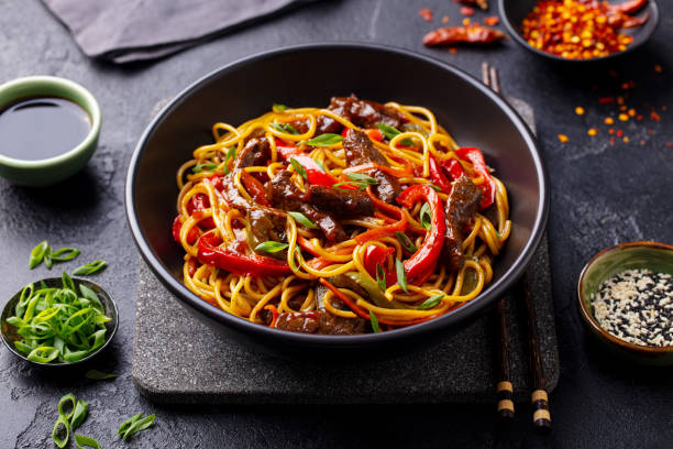 Stir fry noodles with vegetables and beef in black bowl. Slate background. Close up. stock photo