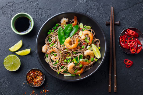Stir fry noodles with vegetables and shrimps in black bowl. Slate background. Top view. stock photo