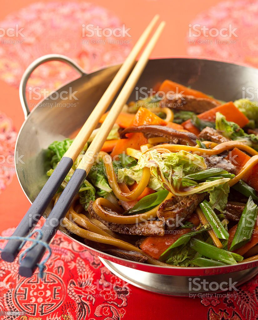 Stir fry prepared on a silver wok with chopsticks royalty-free stock photo