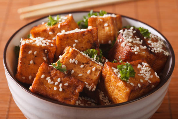 Stir fry tofu with sesame seeds and herbs close-up. horizontal stock photo
