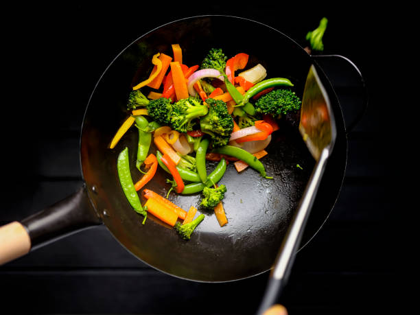 Stir frying and sauteing a variety of fresh colorful market vegetables in a hot wok. stock photo