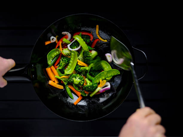 Stir frying and sauteing a variety of fresh colorful market vegetables in a hot steaming wok. stock photo