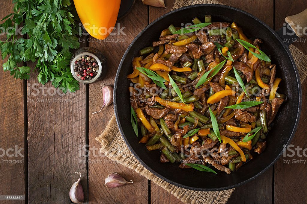 Stir frying beef with sweet peppers and green beans stock photo