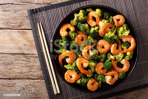 Stir frying shrimp with broccoli closeup on a plate. Horizontal top view from above