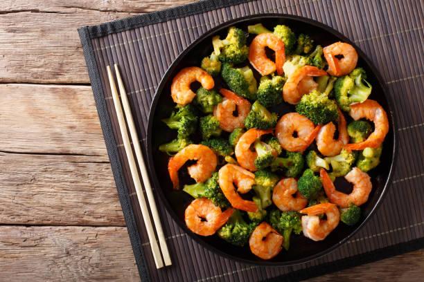Stir frying shrimp with broccoli closeup. Horizontal top view stock photo