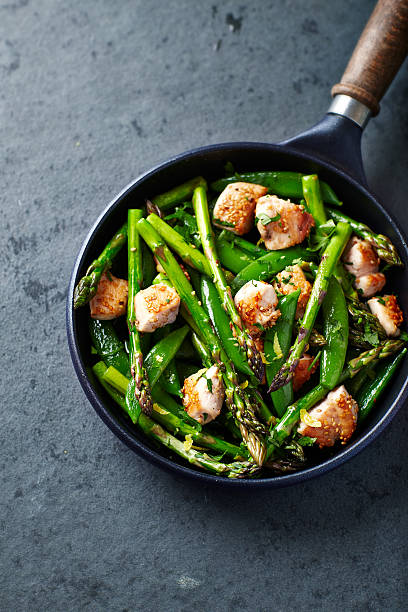Stir-fired sesame chicken, green asparagus and sugar snap peas stock photo
