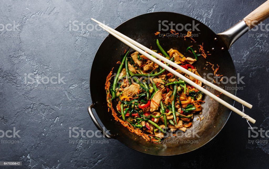 stir-fried chicken with green beans in wok stock photo