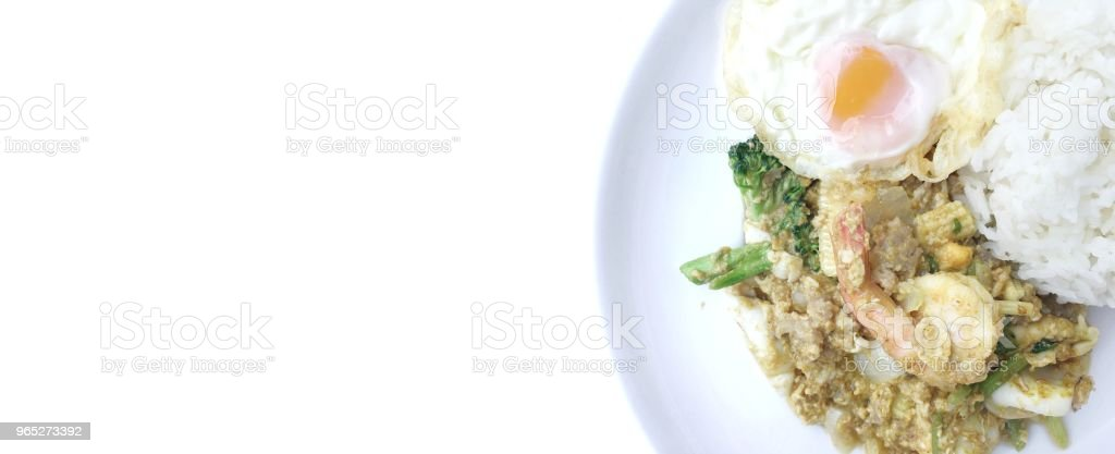 Stir-fried prawns, squi and mixed-seafood with yellow curry powder and thai herb vegetables with rice and fried egg in white plate on white background. Thai style food. zbiór zdjęć royalty-free