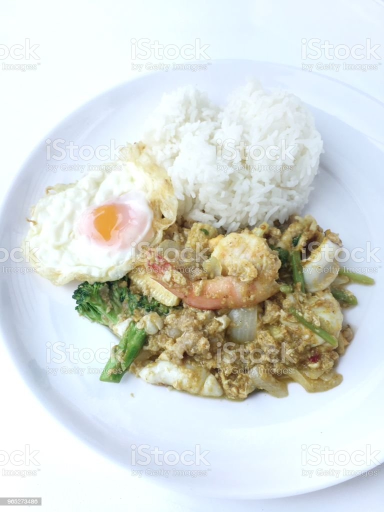 Stir-fried prawns, squi and mixed-seafood with yellow curry powder and thai herb vegetables with rice and fried egg in white plate on white background. Thai style food. royalty-free stock photo