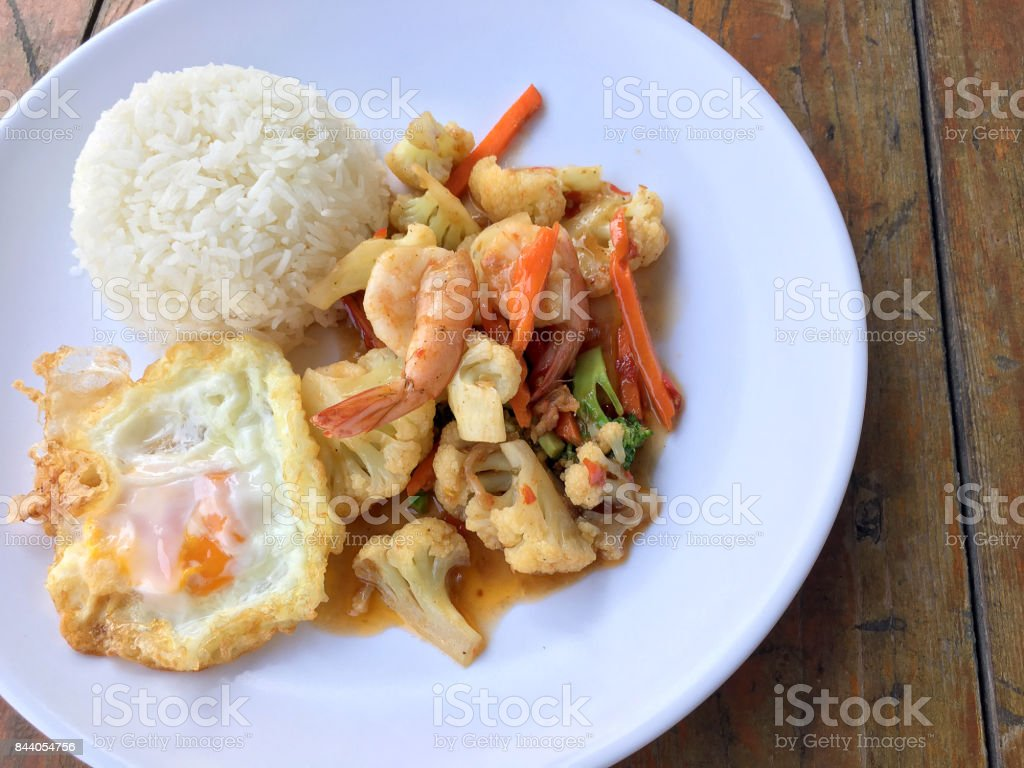 stir-fry vegetables with bean curd and shrimp in white dish with rice and fried egg on wooden background. Thai style Food. stock photo