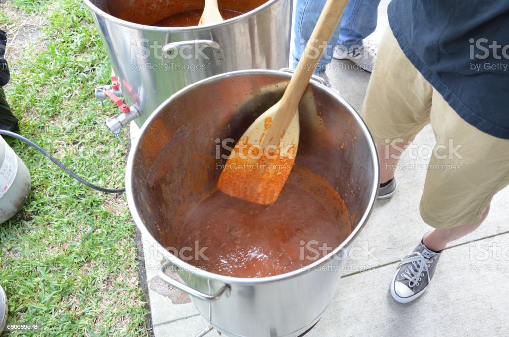 Stirring large batch of chili for competition stock photo