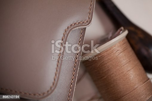 Hand, saddle stitched leather bag closeup with thread spool