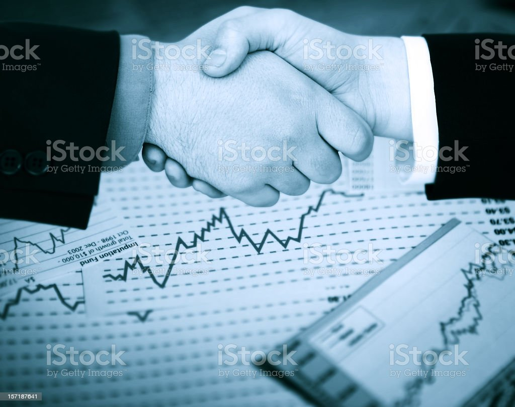 Stock broker shaking hands over stock graphs royalty-free stock photo