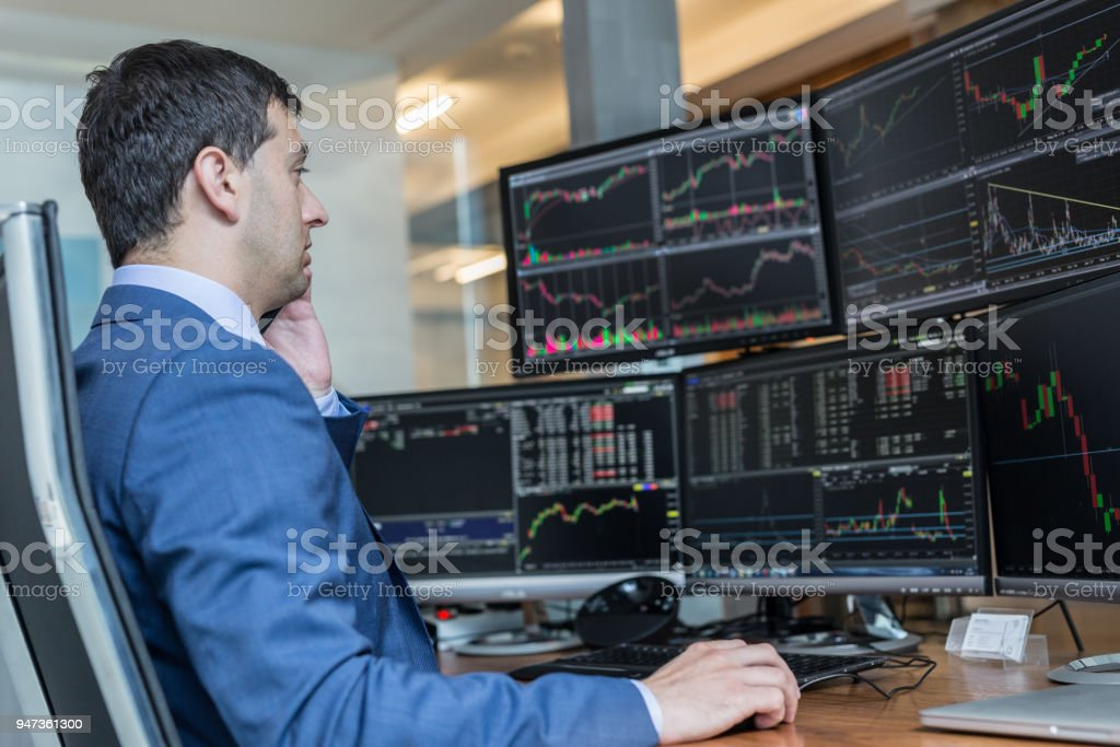 Stock broker trading online watching charts and data analyses on multiple computer screens. Male stock broker trading online watching charts and data analyses on multiple computer screens. Adult Stock Photo