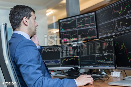 istock Stock broker trading online watching charts and data analyses on multiple computer screens. 947361300